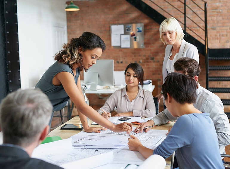 A group of coworkers surrounding a table looking at a papers on the table.