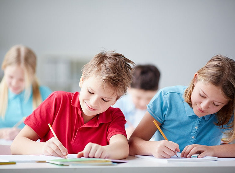 A young girl and boy sitting beside each other at a desk writing in notebooks.