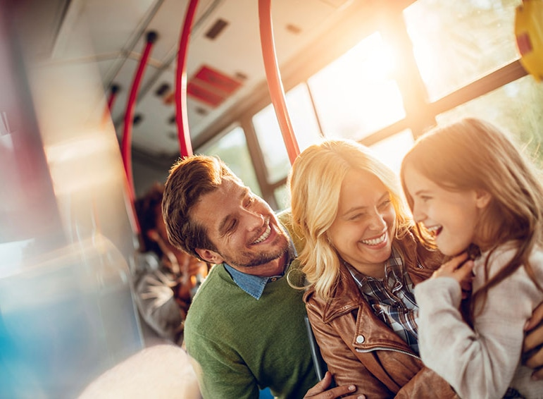 A family smiling and laughing, sitting on the bus with a bright, sunny background.