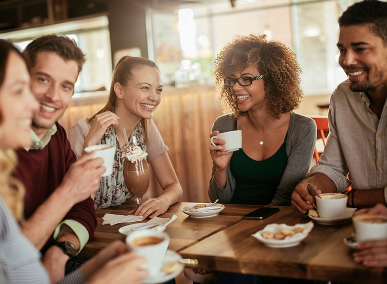 A group of friends happily drinking coffee around a table in a cafe.