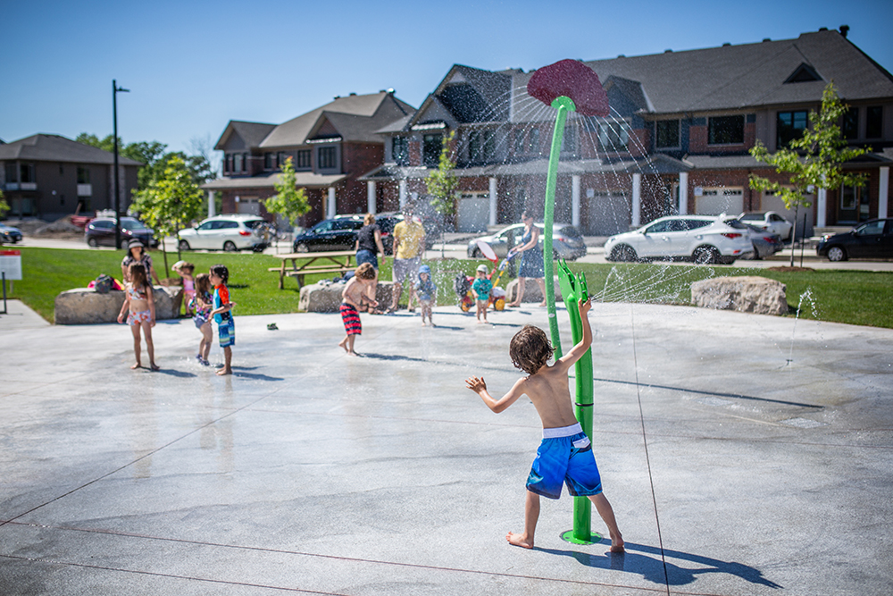 A small boy playing at an outdoor water playground. Houses line the background.